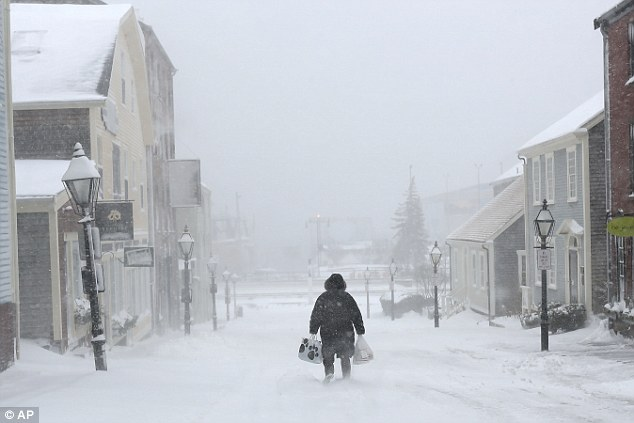 A woman walks down the street in New Bedford, Massachusetts on Monday during a snowstorm