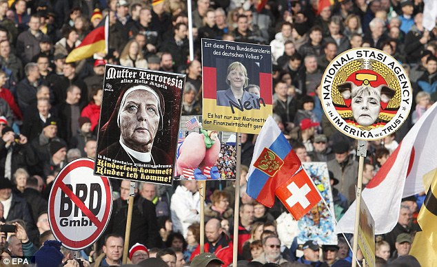 Offensive: Pegida banners showing the face of Chancellor Angela Merkel depicted as a pig and a nun