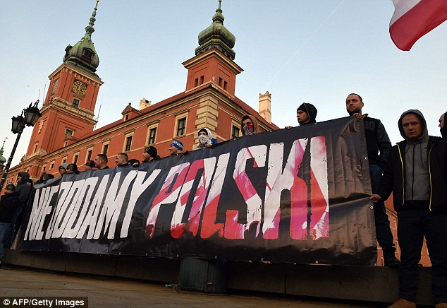 Aggression: Pegida supporters in Warsaw display a banner reading 'will not give back Poland'