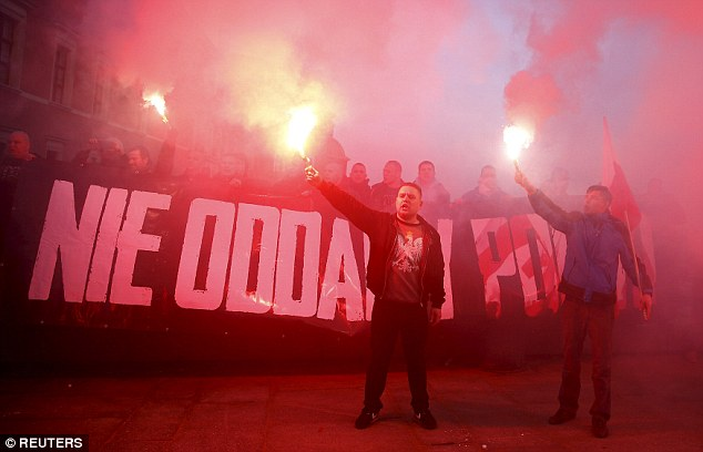 Hooligans: Protesters let off flares during a Pegida rally in front of the Royal Castle in Warsaw, Poland