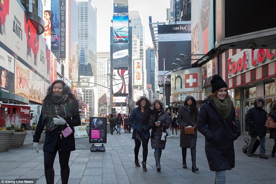 People in Times Square wrapped up and trying to keep warm on Saturday as wind chill in New York City reached as low as minus-36