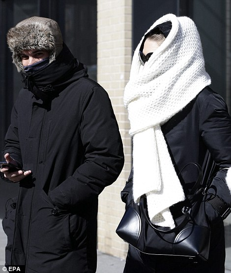 A couple braces themselves against the cold as temperatures approach zero degrees