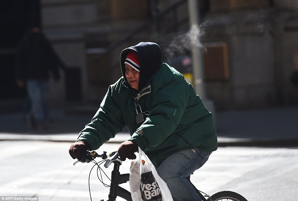 Despite the cold, one man faced the wind head-on as he rode a bicycle through downtown Manhattan on Sunday