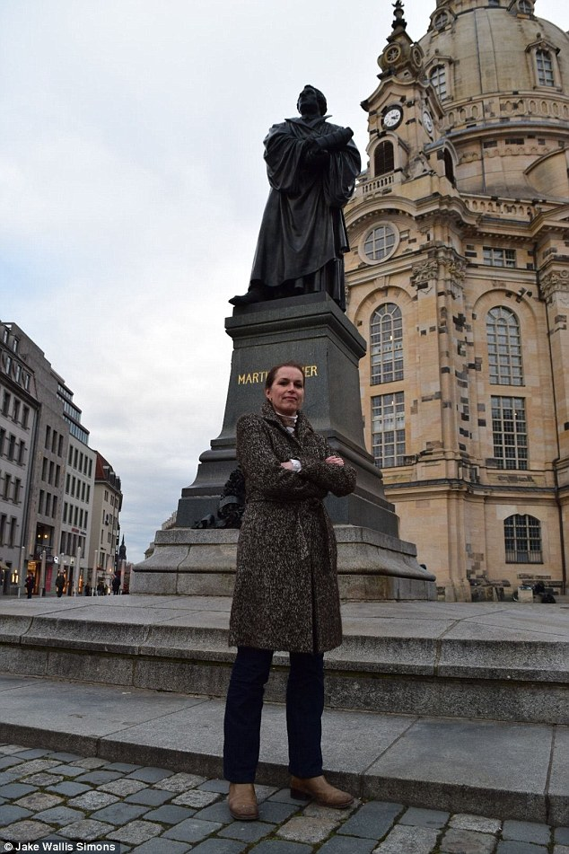 Determined: Festerling poses in front of a statue of Martin Luther in Dresden. She cited his 1521 statement, 'here I stand. God help me. I can do no other'