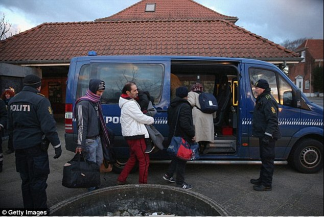 Danish police escort a family from Syria seeking asylum in Denmark after finding them while checking the identity papers of passengers on a train arriving from Germany in Padborg last month. A  new law forcing migrants in Denmark to hand over  valuables to fund their benefits didn't raise a single penny in its first week
