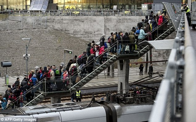 Police organise a line of refugees on the stairway leading up from the trains arriving from Denmark at the Hyllie train station outside Malmo, Sweden.Denmark had previously been seen as more of a thoroughfare until Swedenintroduced a cap on migrants, meaning more asylum seekers are now staying Denmark