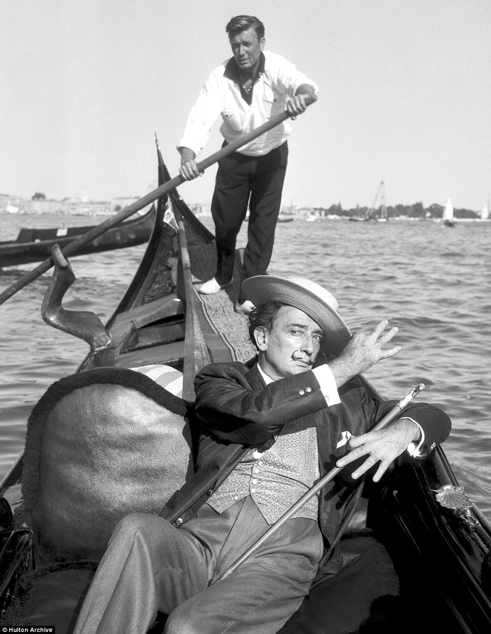 Spanish artist Salvador Dali pulls a dramatic pose on a gondola while the gondolier rows on behind him
