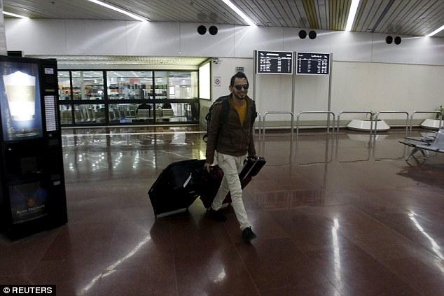 Un refugiado iraquí sonríe y hoy saca su equipaje del aeropuerto de Bagdad