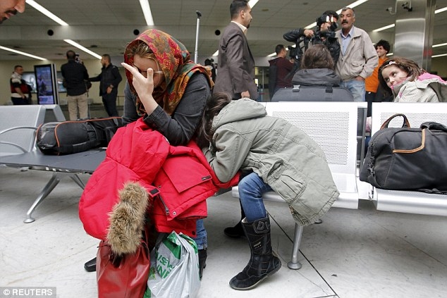 Una mujer y su hija rompen en llanto de alivio al regresar hoy a Bagdad