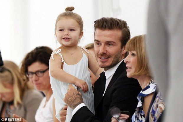 So cute: Pictured looking trendy aged three with her father David at her mother's spring/summer collection in NY in September 2013