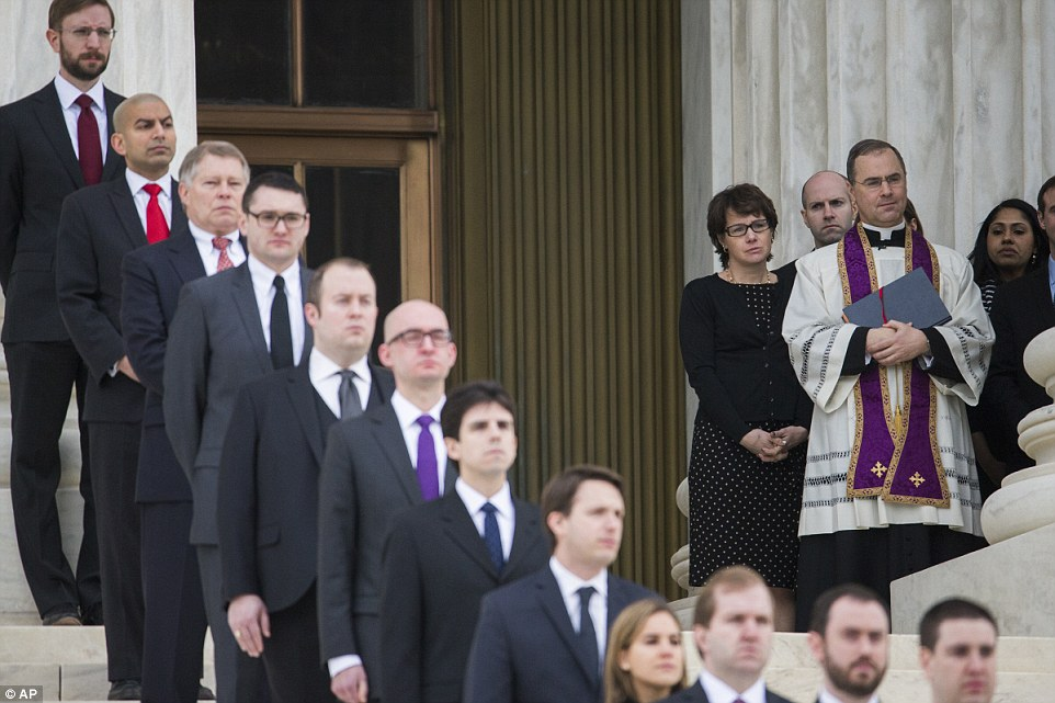 Father Paul Scalia (right) watched as his father's casket, which was draped in the American flag, was carried up the court's steps