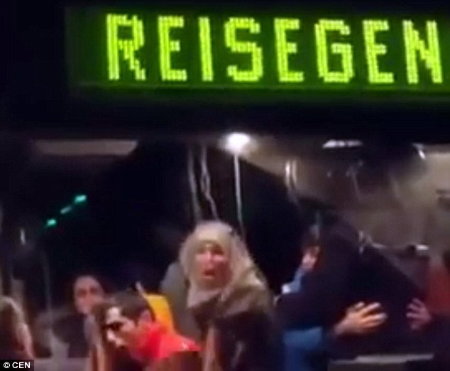 Anger: Dramatic footage appears to show a refugee woman (centre) spitting at the anti-migrant protesters who had swarmed around their bus