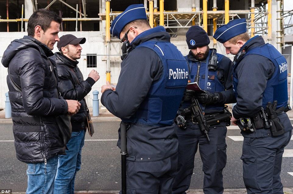 Echando un vistazo: Los agentes de policía comprobar los pasaportes de los dos hombres hoy en su intento de cruzar la frontera franco-belga en Adinkerke, Bélgica