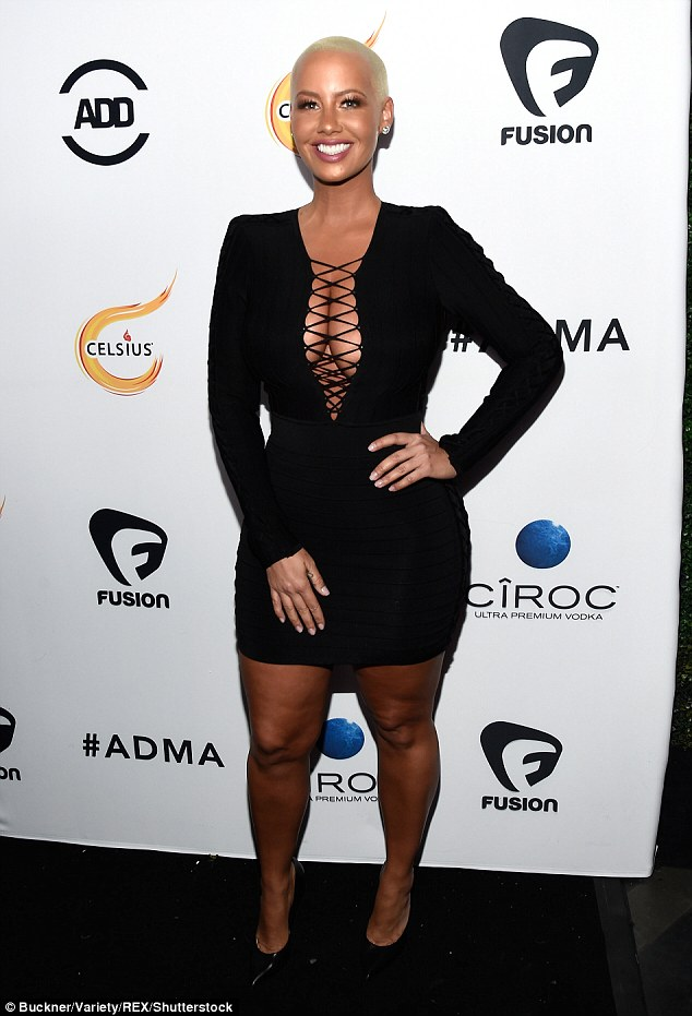 Saucy and sexy:The model dared to bare in a tight black mini dress with long sleeves which would have been an impressive showcase for her famous curves on its own, but Amber decided oi take it up a notch