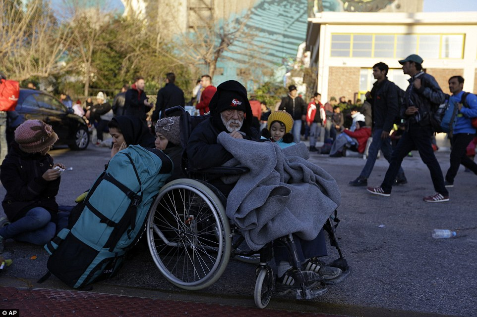 An elderly refugee in a wheel chair waits along with other migrants at the Athens port of Piraeus this morning