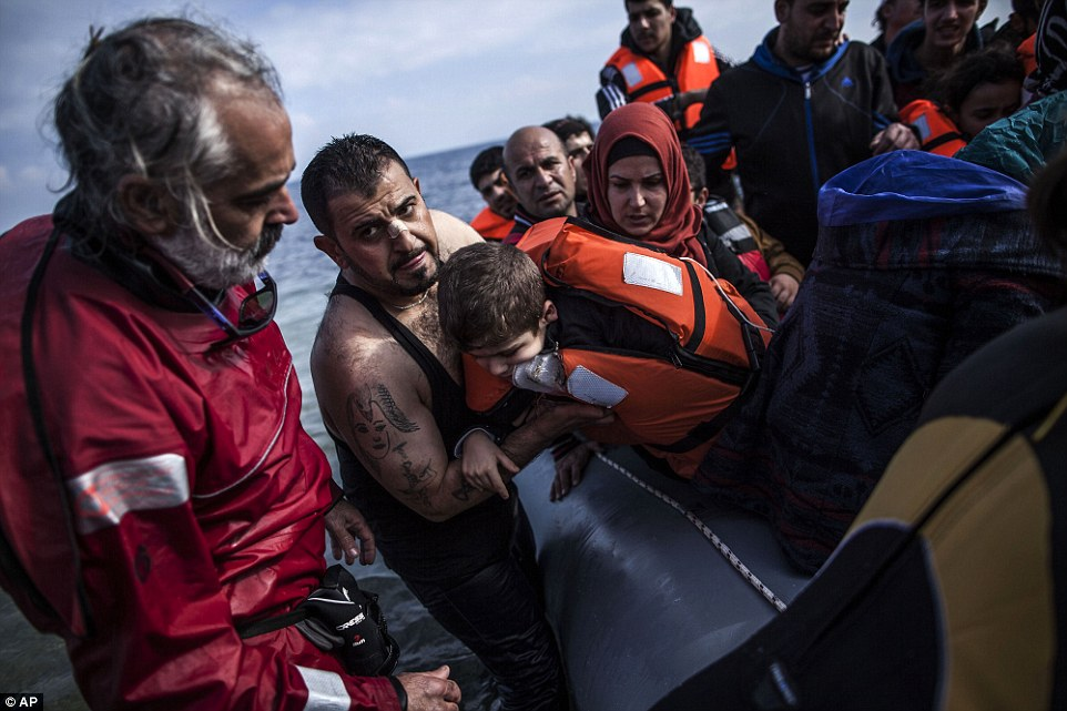 A Syrian man holds his son as they arrive with refugees and migrants on a dinghy from the Turkish coast to Mytilen