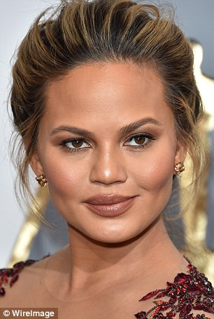 Tinted bliss: Chrissy Teigen showed off champagne tinted diamonds on her earrings and rings totaling $2.8 million
