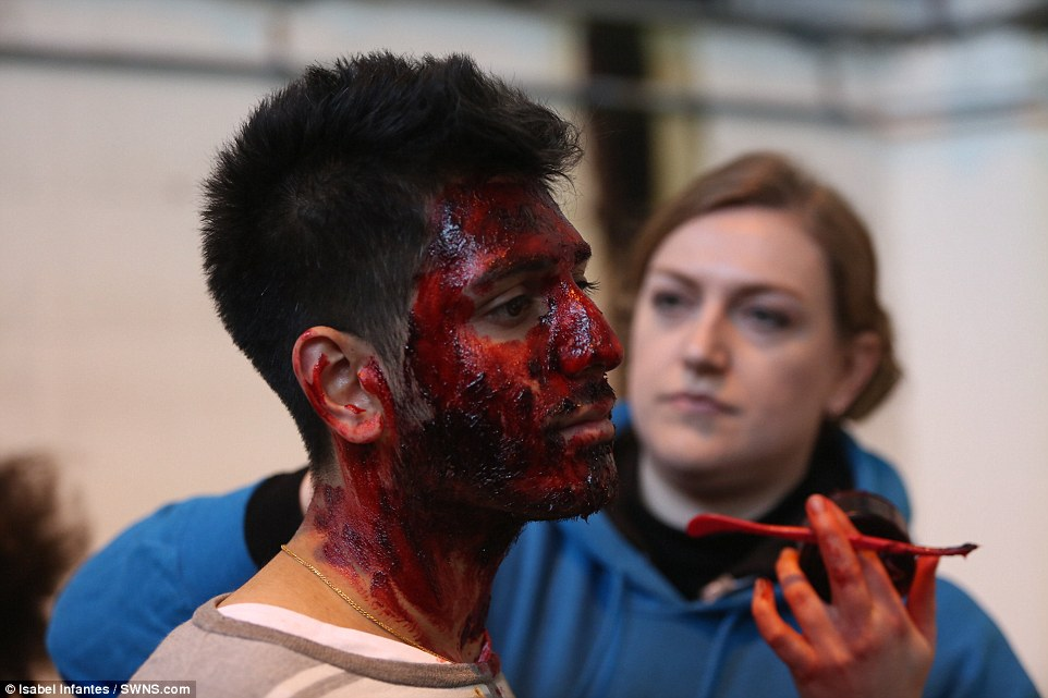 Playing the part: An actor has his face covered in stage make up as he prepares to play a casualty of the would-be disaster in London