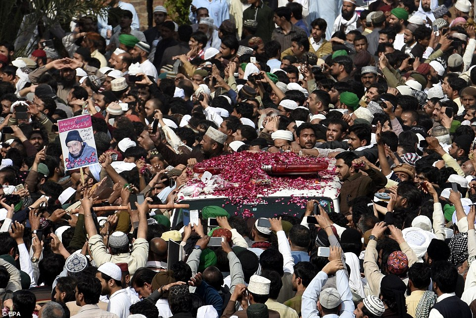 Qadi's coffin was carried through Rawalpindi today (pictured) before tens of thousands of supporters as they threw rose petals on its roof