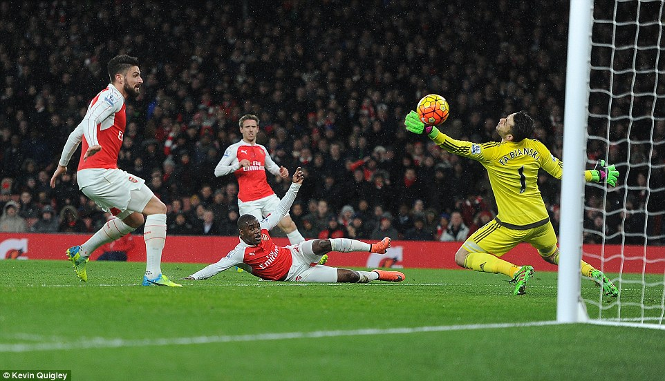 Arsenal's Joel Campbell slides on the ground after getting his left foot to the ball to propel past Swansea City's Lukasz Fabianski