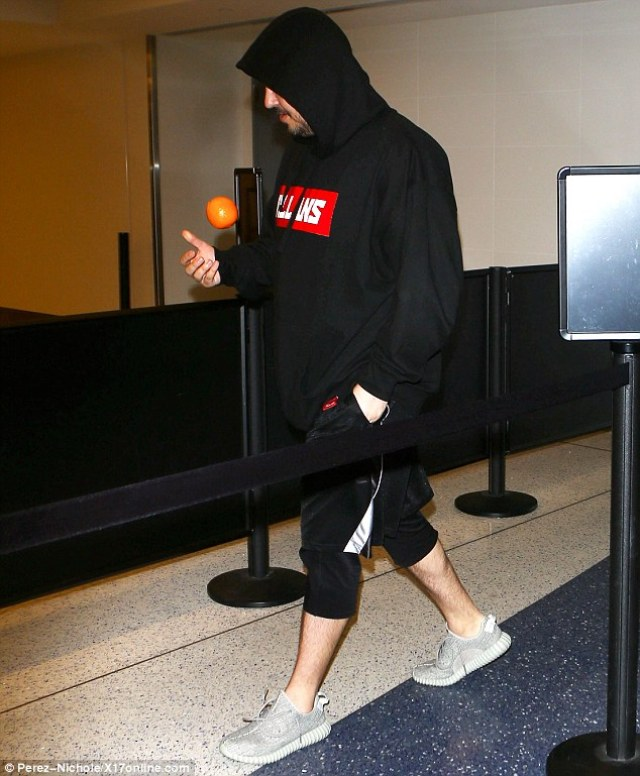 Healthy snack: Rob was seen clutching an orange as he made his way through the terminal