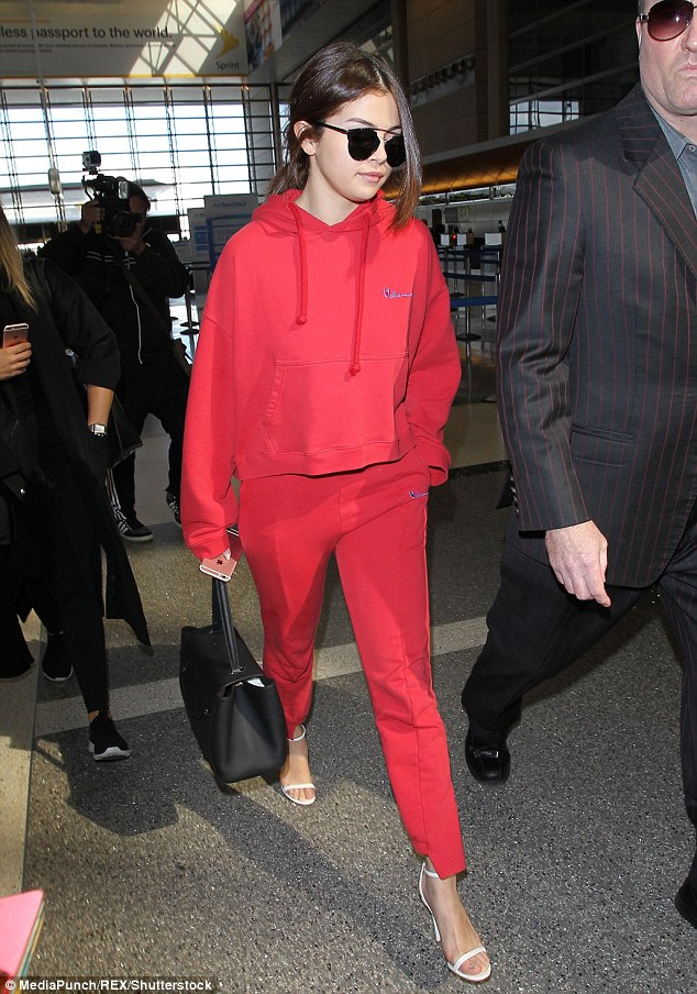 A change of footwear: Selena was spotted arriving at Los Angeles' LAX Airport late on Monday to catch her flight to Paris, adding stylish touch to her crimson outfit with a pair of white strappy stilettos
