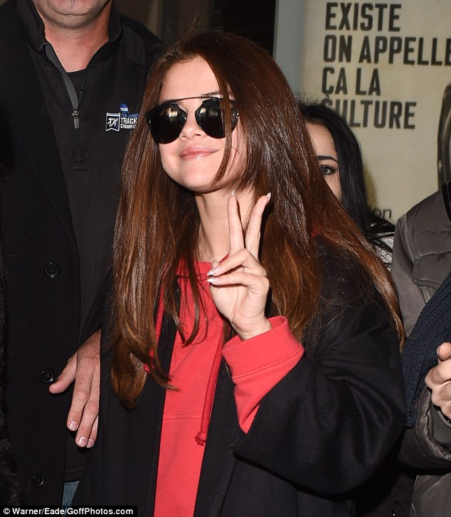 Peace! Flashing a peace sign as she made her way to the hotel, the ex-girlfriend of Justin Bieber wore her brunette locks straight around her shoulders and toted her belongings in a black leather oversized bag