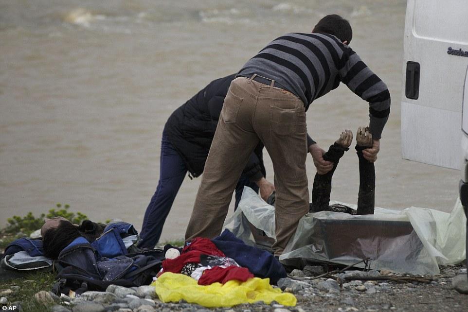 forenses macedonias colocan el cuerpo del migrante ahogado en un ataúd en la orilla del río del río Suva Reka cerca de la ciudad meridional de Macedonia Gevgelija, después de que él y otros dos trataron de cruzar la frontera con Grecia