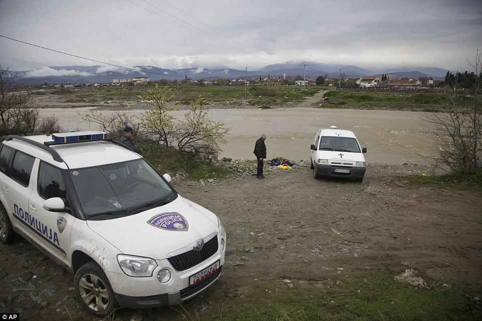 Un oficial de policía macedonia mantiene la zona en la que los cuerpos de los migrantes ahogados se encuentran en la orilla del río