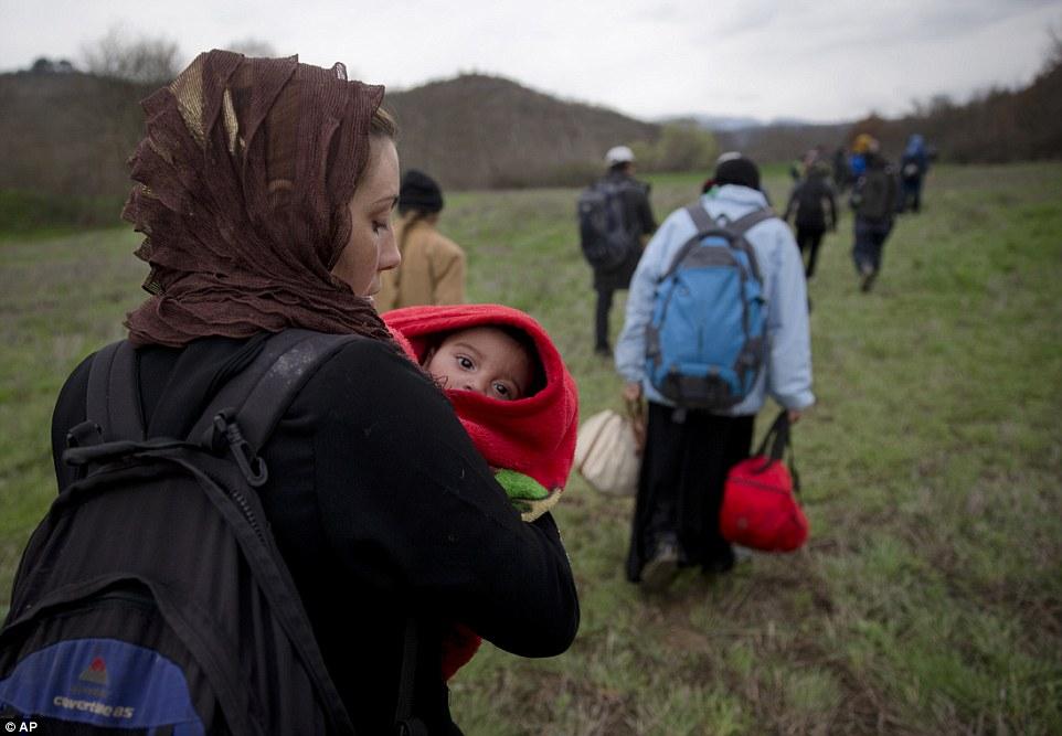 En la foto, un grupo de migrantes viaje a través de un campo en Macedonia después de pasar por un muro en la frontera mediante la negociación del río traicionero
