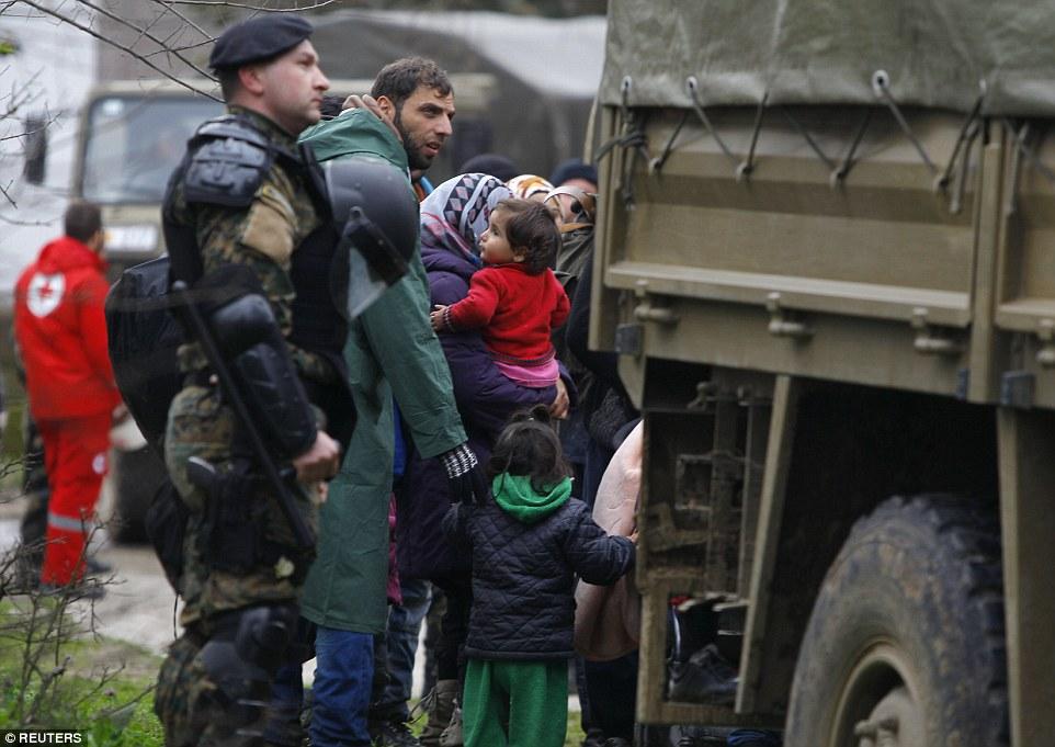Arresto es un riesgo que enfrentan todos los migrantes y la foto, soldados macedonios escolta de una familia que han cruzado la frontera ilegalmente desde Grecia
