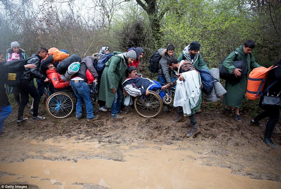 Los migrantes ayudan a las personas en sillas de ruedas a través del río después de la decisión de cerrar su frontera dejó a miles de personas en el campo de tránsito griego