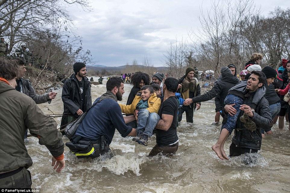 Cientos de inmigrantes llevaron a los niños y sillas de niños, ya que se metieron en el agua hasta los muslos de profundidad para llegar a una brecha en la valla fronteriza