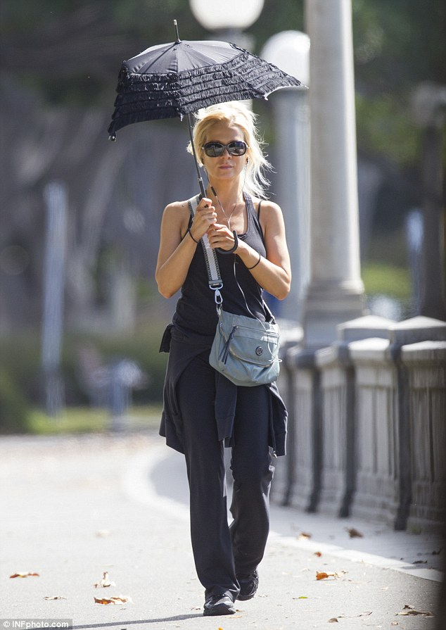 Russell Crowes estranged wife Danielle Spencer enjoys stroll beneath a black frilly parasol