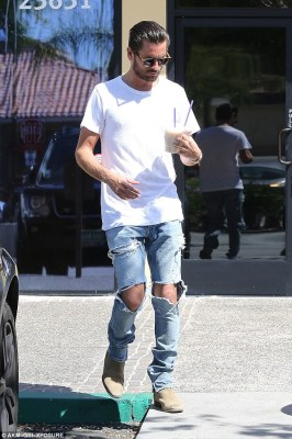I'm with the band: Disick looked a bit rockerish in his ripped denim jeans and white T-shirt with roughed-up beige suede boots