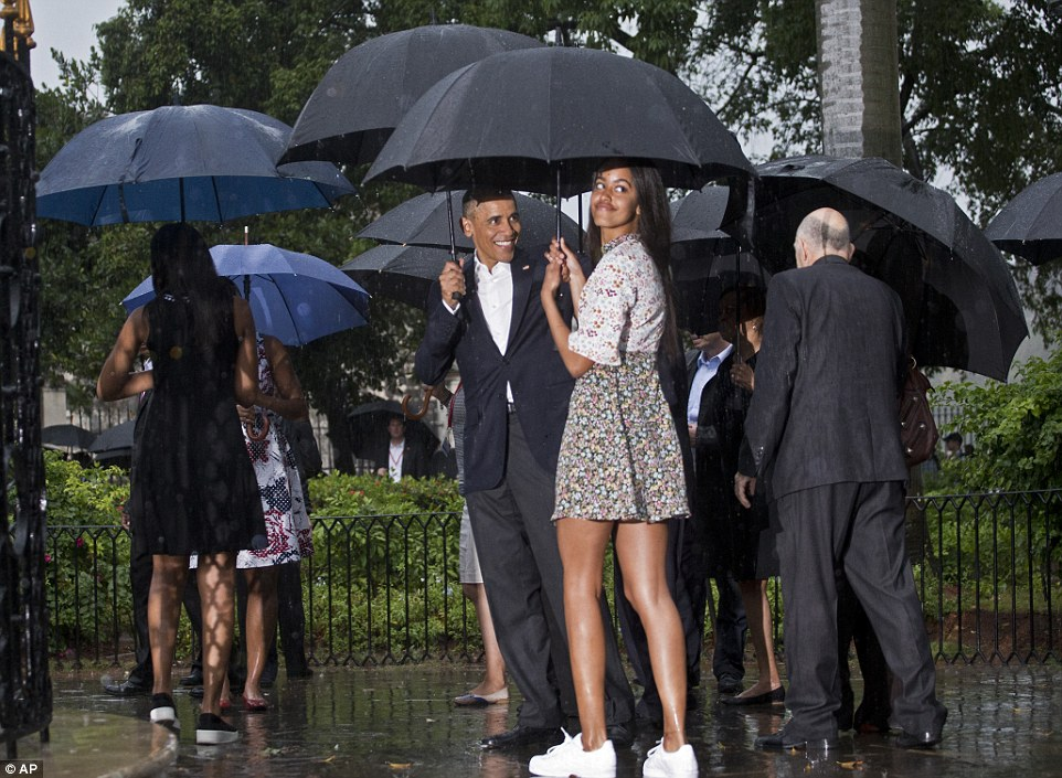 Family outing:The first family pressed on, despite the stormy skies, strolling through the Plaza des Armas as they huddled under their umbrellas as they made their way to the Museo de la Ciudad, the museum of the Cuba's capital city