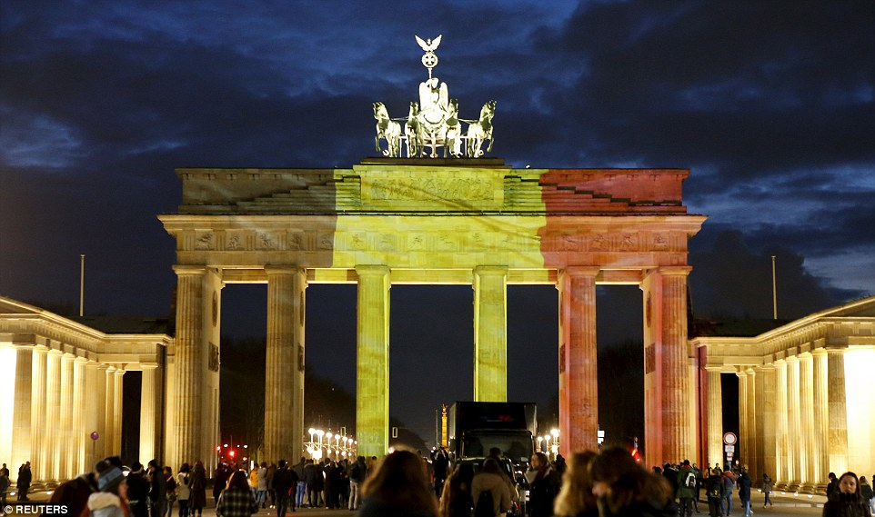 Tribute: People stood in front of the Brandenburg gate in Berlin, which is illuminated in the colours of the Belgian flag this evening