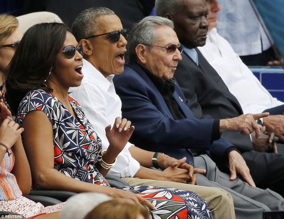 Let's play ball: Barack and Michelle Obama react to a play during the baseball, while Raul Castro sits impassively