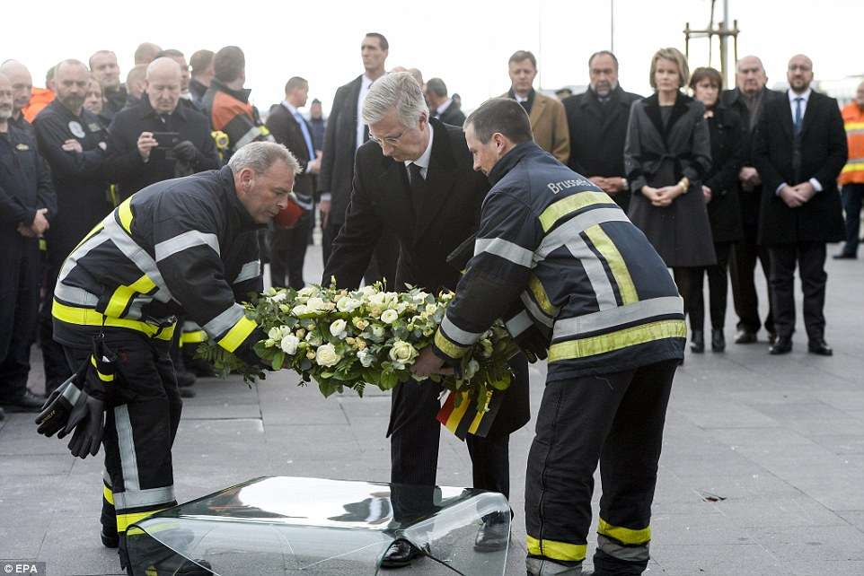 En la memoria: el rey Felipe de Bélgica (centro), establece una corona mientras se visita la zona de salidas dañado en el aeropuerto de Bruselas en Zaventem
