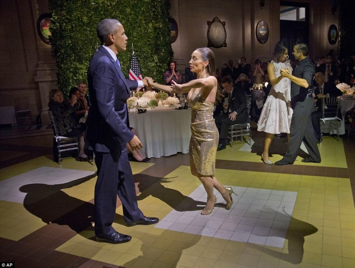 President Barack Obama and first lady Michelle Obama dance with tango dancers during the State Dinner at the Centro Cultural Kirchner