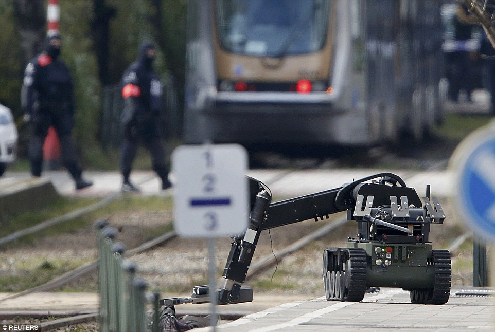 Police use a robotic device as they take part in a search in the Brussels borough of Schaerbeek following Tuesday's bombings in Brussels
