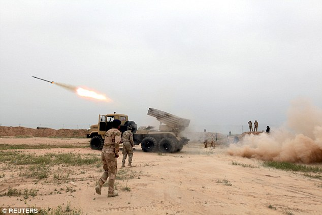 A Russian soldier died in an airstrike that he directed on himself after finding himself surrounded by ISIS militants near Palmyra. Pictured, Iraqi soldiers fire a rocket toward ISIS fighters on the outskirt of the Makhmour south of Mosul, Iraq