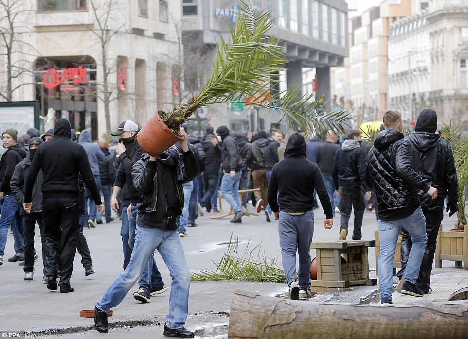 Vandals kicked over bins and launched plant pots through the air as they retreated following the police advance this afternoon