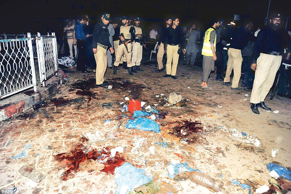 Pakistani emergency workers and police officers gather at the blast site, where 300 people were injured