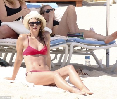 Chilling out:Looking as though her woes were a million miles away, Maria larked around on the shores while showing off her incredible athletic physique in her tiny two-piece