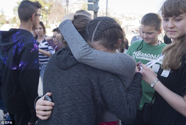 Two students hug after being evacuated from the building, apparently with a school group