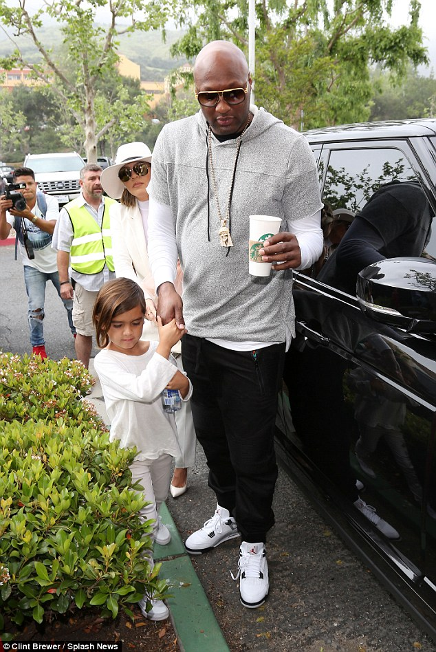 Close and cozy: Lamar held onto Mason's hand as ex Khloe followed closely behind