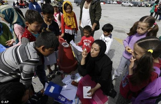 University teacher Ziaee Shole, center, speaks to Afghan refugee children at the Athens port of Piraeus