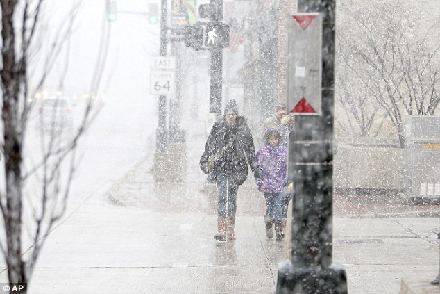 Snow, rain, sun, and winds gusting to more than 50 mph hit the Fox Valley area Saturday as people make their way along Main Street in St. Charles, Illinois