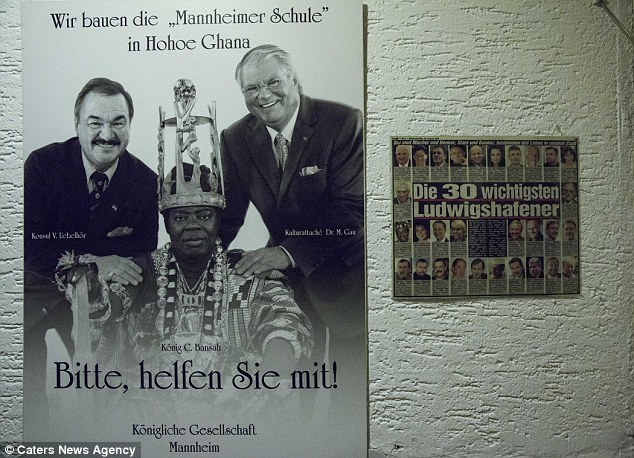 His garage wall features a promotional poster which asks for help building a school in his birthplace, Ghana